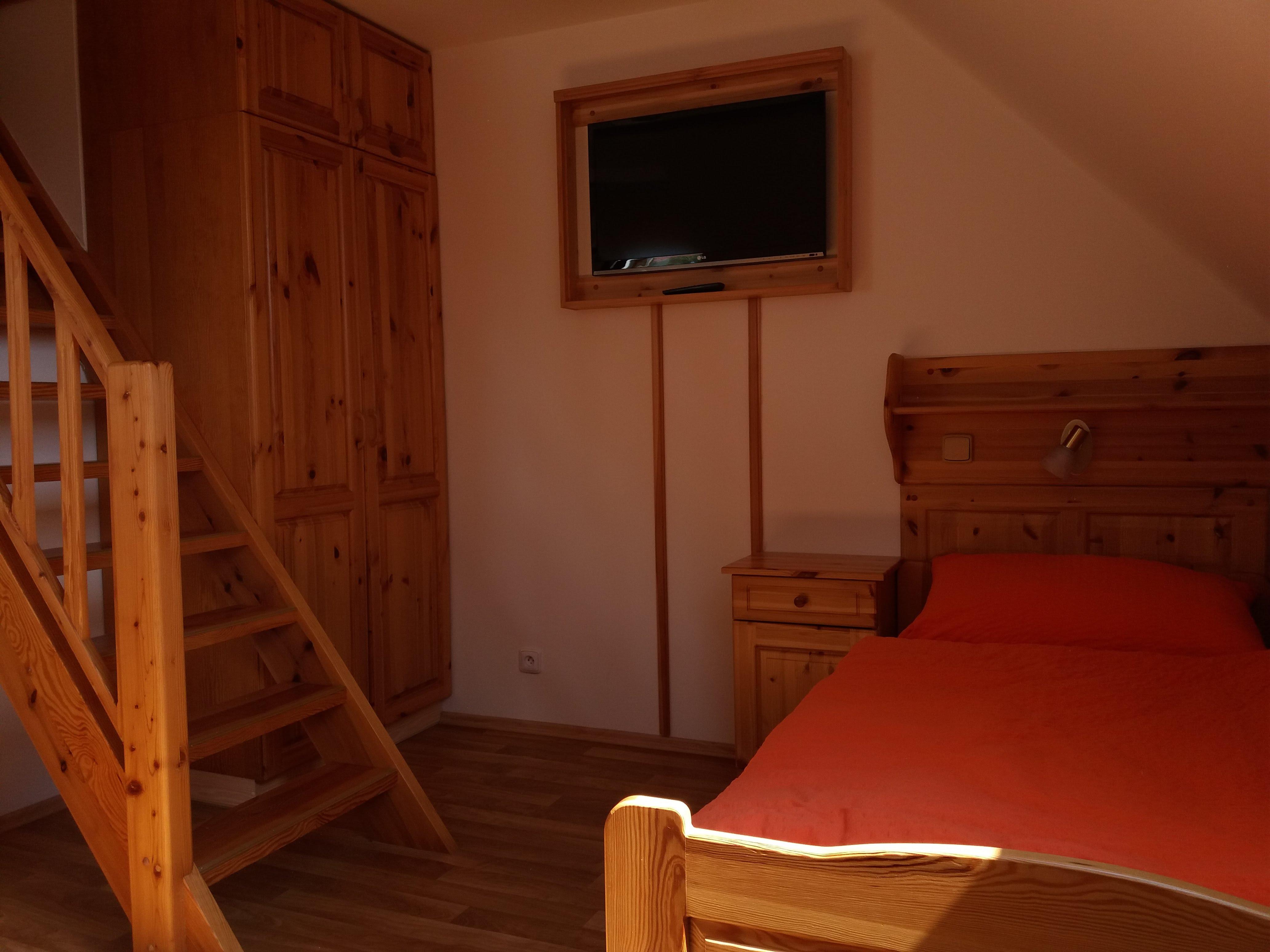 Jedna z postelí a schody do podkrovní části pokoje