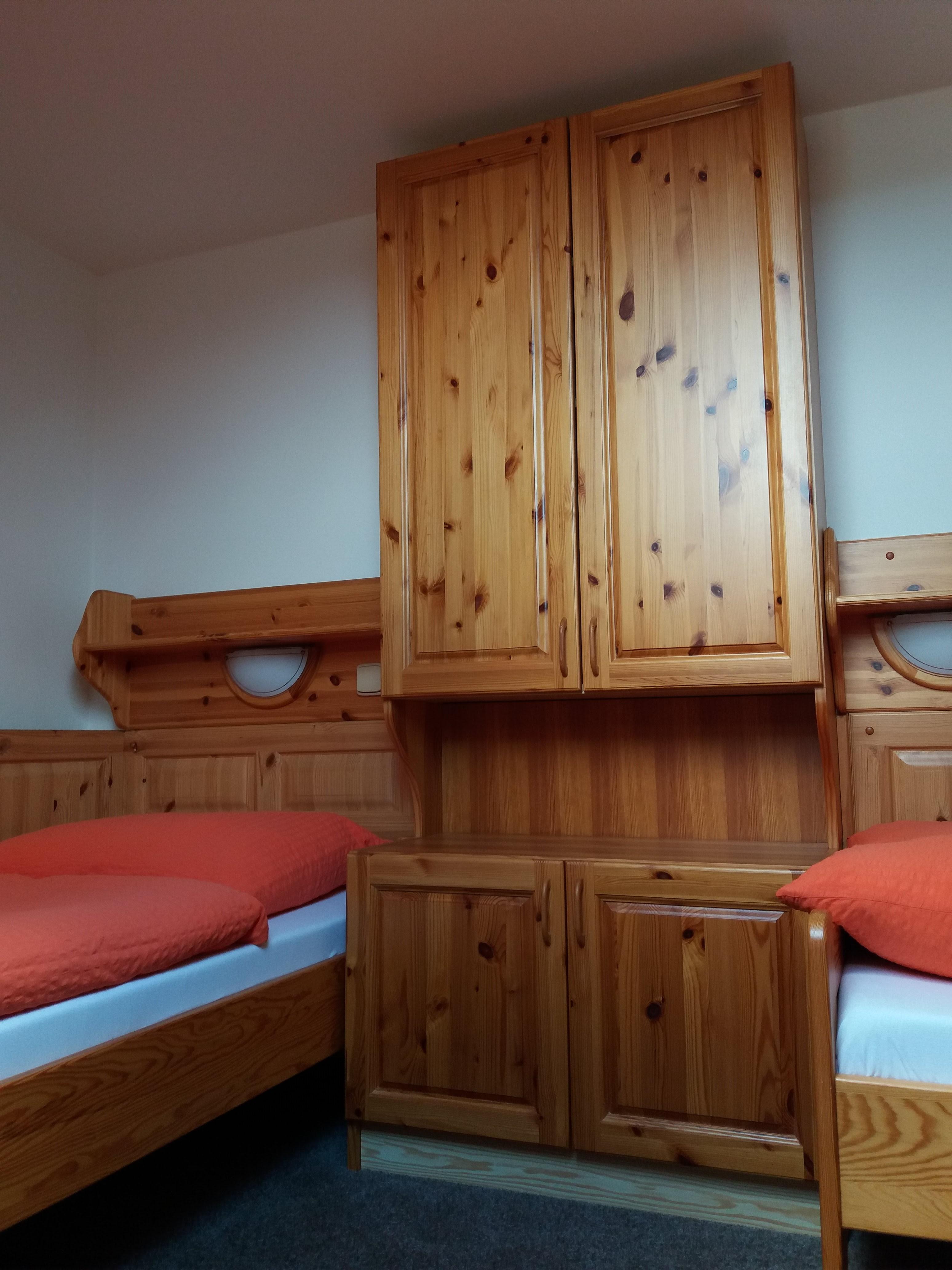 Postele a skříň v podkrovní části pokoje