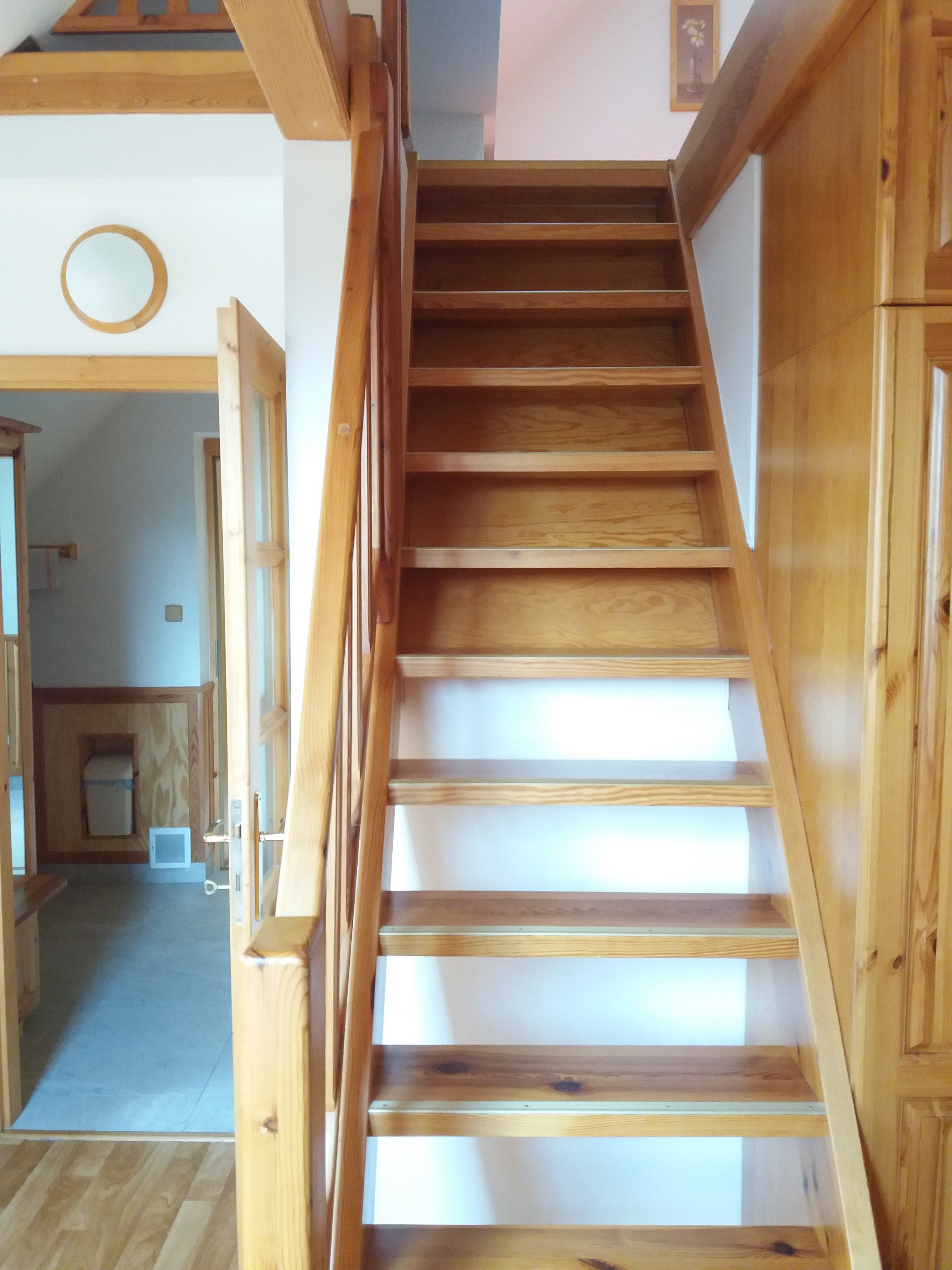 Schody do podkrovní části pokoje, vlevo průchod přes kuchyňský kout ven z pokoje