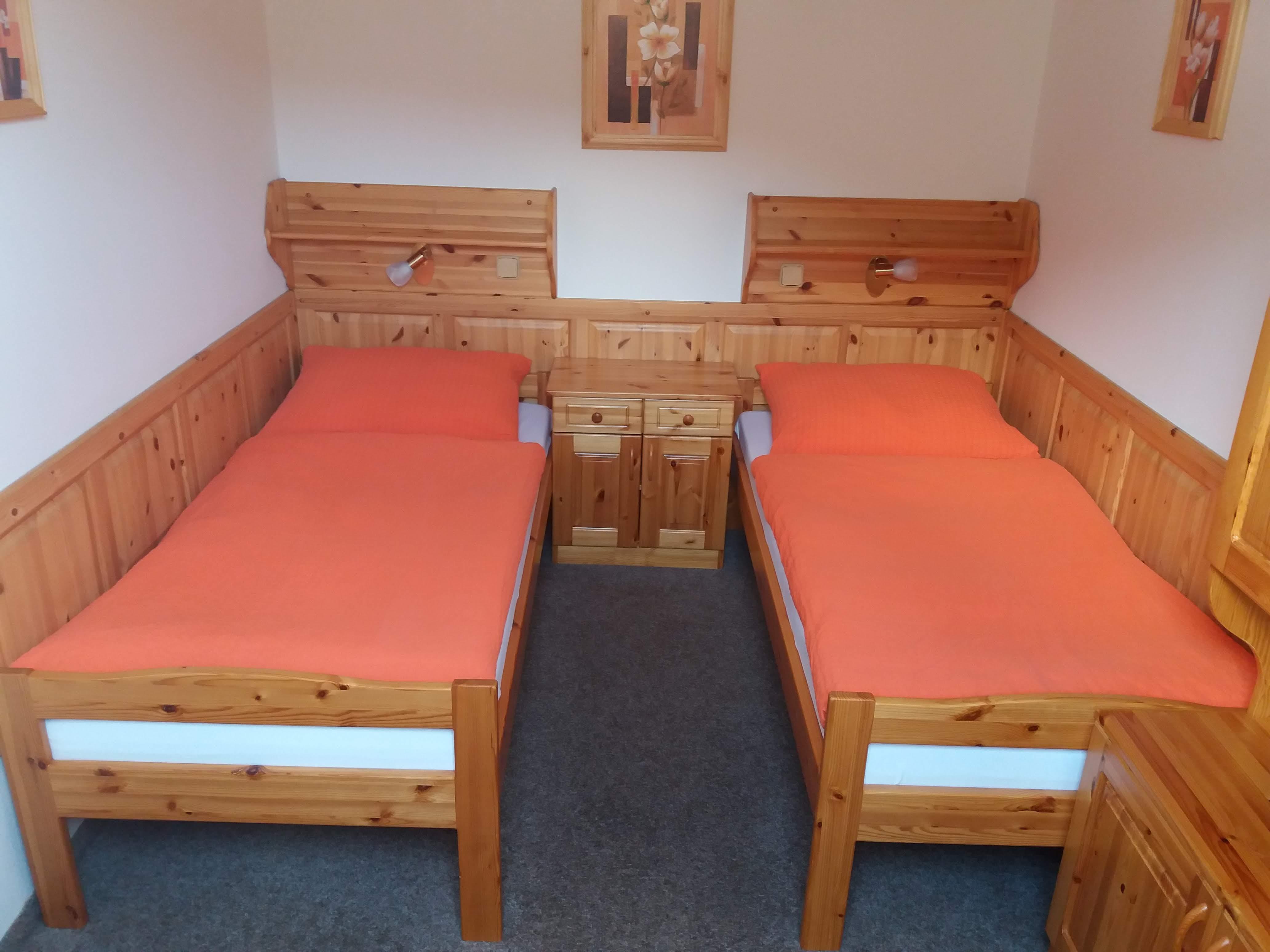 Postele v podkrovní části pokoje