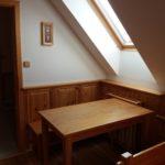 Jídelní stůl a vstup do pokoje (vpravo kuchyňský kout)